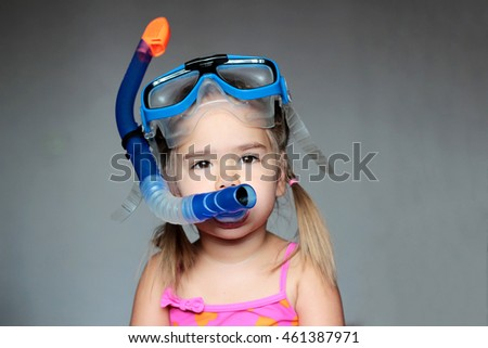 Little girl wearing a diving mask over grey background, swim and sport concept