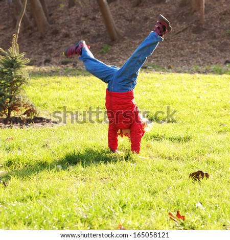 Little girl wearing a red standing on hands upside down on green grass. Active and healthy lifestyle concept. - stock photo