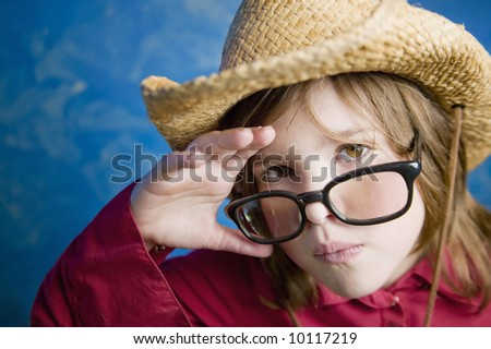 Little girl wearing a straw cowboy hat adjusts her glasses - stock photo