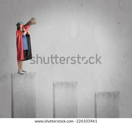 little girl wearing a superhero costume shouting with an old megaphone on the top of a chart - stock photo