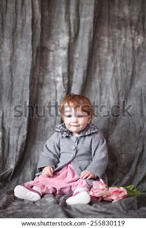 Little girl wearing autumn grey coat, over gray background - stock photo