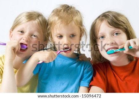 Little girl wearing colorful t-shirts brushing teeth - stock photo