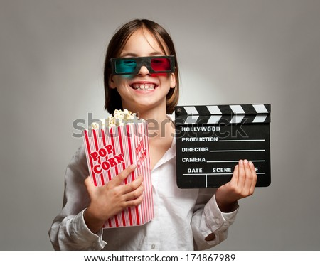little girl wearing 3D glasses and eating popcorn - stock photo