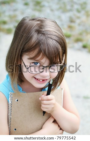 Little girl wearing glasses with pen and book. Shallow depth of field with selective focus on child's face.