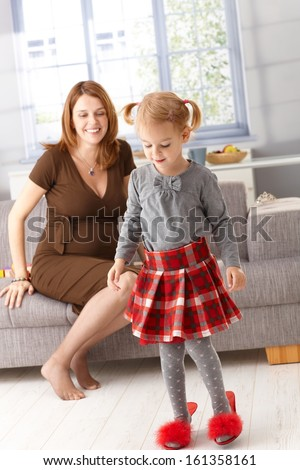 Little girl wearing mother's high heel red slippers, pregnant mother watching from background. - stock photo