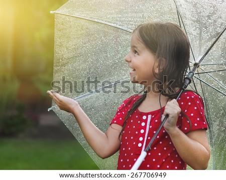 Little girl wearing polka dots dress under umbrella in rainy day - stock photo