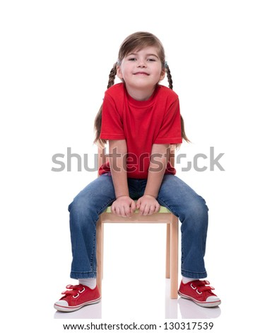 little girl wearing red t-shirt and posing on chair isolated on white