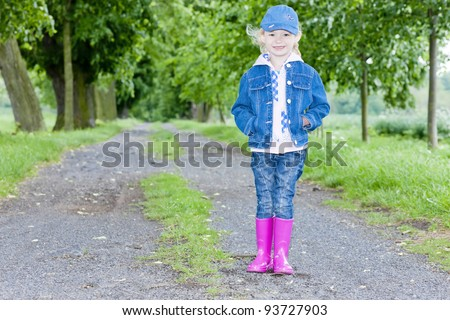 little girl wearing rubber boots in spring alley