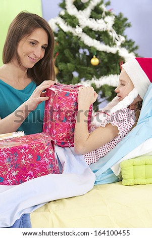 little girl wearing Santa hat receiving her gift while she is in hospital - stock photo