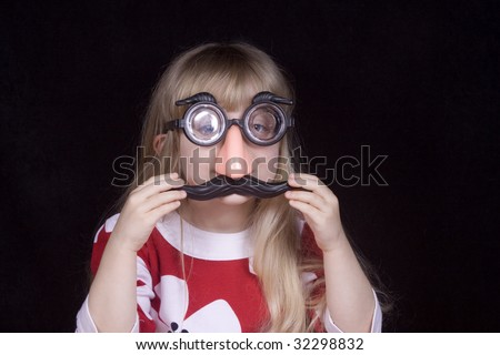 Little girl wearing silly mustache glasses. - stock photo