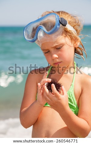 Little girl wearing snorkeling mask looking at sea urchin, focus on hands - stock photo