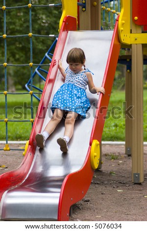 Little girl wearing spotted blue-white dress and braids sliding on children's chute