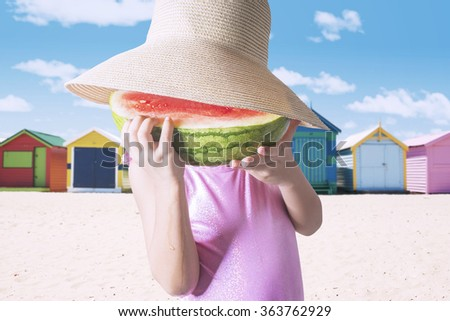 Little girl wearing swimsuit and eating a slice of watermelon at the beach - stock photo