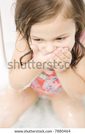 Little girl wearing swimsuit playing i the bathtub