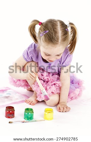 Little girl wearing tutu skirt drawing with watercolors - stock photo