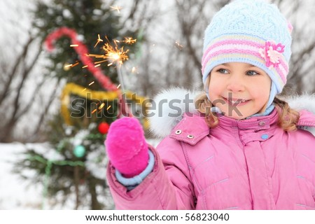 little girl wearing winter jacket is standing near christmas tree with bengal light. christmas tree in out of focus.