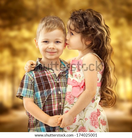 Little girl whispering something to boy and holding his hands. Love concept - stock photo