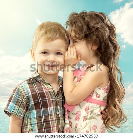 Little girl whispering something to boy on blue sky. Love concept - stock photo
