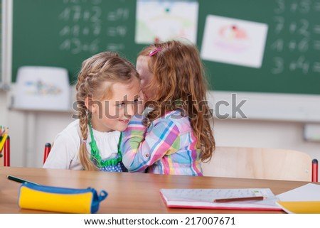 Little girl whispering to her beautiful young friend in class at school telling her a great secret or gossiping about a classmate, chalkboard and notices background - stock photo