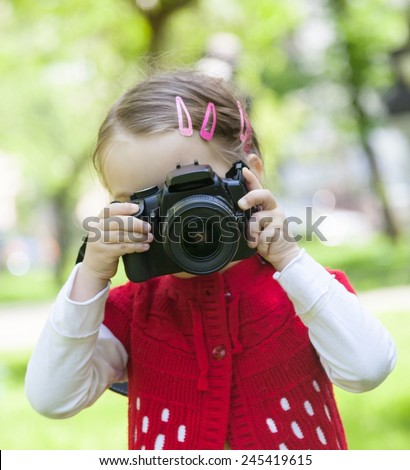 Little girl who takes pictures with a photo camera in park - stock photo