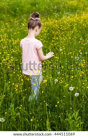 Little girl who walks through the garden - stock photo