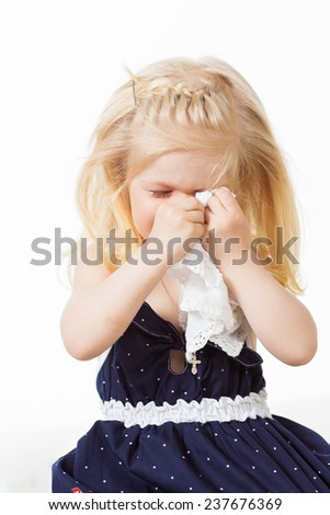 Little girl wiping her eye with handkerchief - stock photo