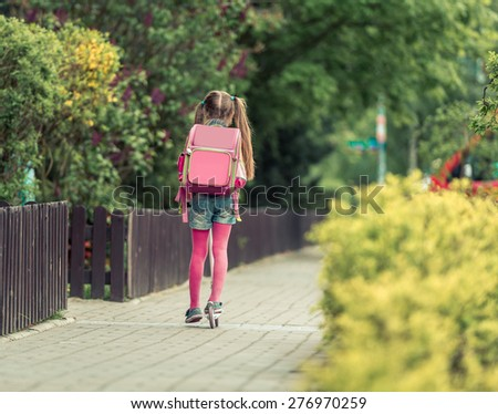 Little girl with a backpack goes to school on a scooter. back view - stock photo