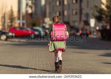 little  girl with a backpack going to school - stock photo