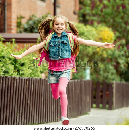 little girl with a backpack run from school - stock photo