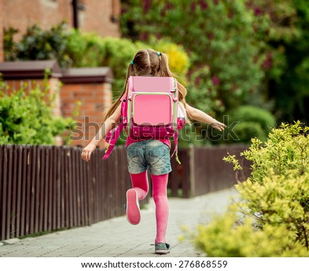 little girl with a backpack run  to school. back view - stock photo