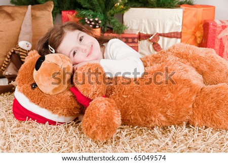 Little girl with a big teddy bear at Christmas - stock photo