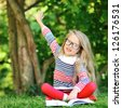Little girl with a book in a park wearing glasses pointing at copyspace - stock photo