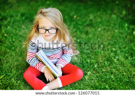 Little girl with a book in a park wearing glasses portrait - stock photo
