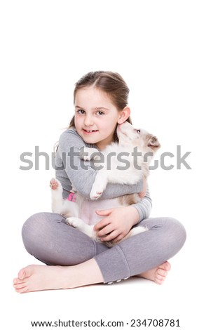 little girl with a border collie in front of a white background