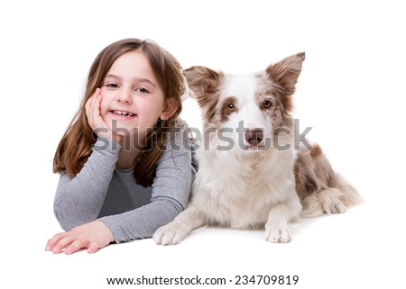 little girl with a border collie in front of a white background - stock photo