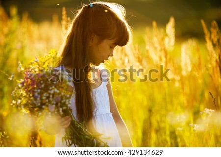 Little girl with a bouquet of wild flowers - stock photo