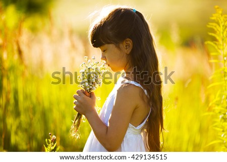 Little girl with a bouquet of wildflowers - stock photo