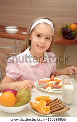 Little girl with a cheerful mood eating an omelette - stock photo