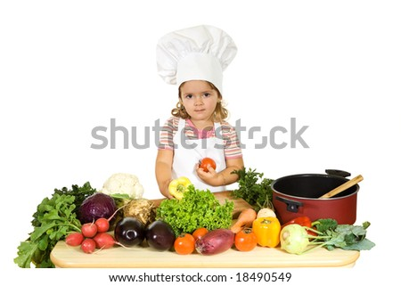 Little girl with a chefs hat, apron and lots of vegetables - isolated