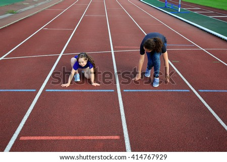 Little girl  with a coach on the stadium