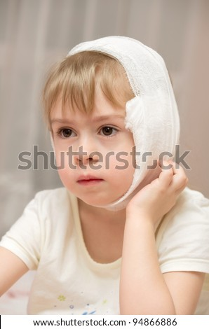 Little girl with a compress on the sore ear. - stock photo