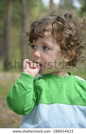 Little girl with a curiosity for someone watches and keeps his finger in his mouth. - stock photo