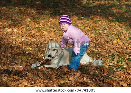 Little girl with a dog in the park in autumn - stock photo