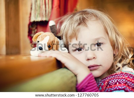 Little girl with a dog toy is leaning on the window - stock photo