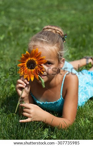 Little girl with a flower in summer time - stock photo