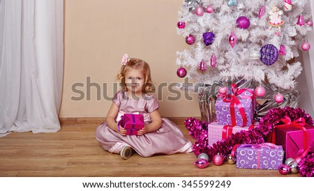 Little girl with a gift near the Christmas tree. New Year. Holiday and fun. Merry Christmas. 2017 - stock photo