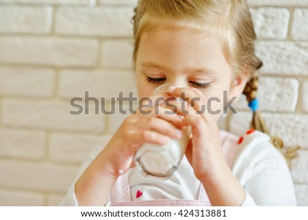 little girl with a  glass of milk - stock photo