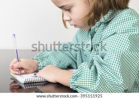 Little girl with a green plaid smock writing and drawing in a notebook at home - stock photo