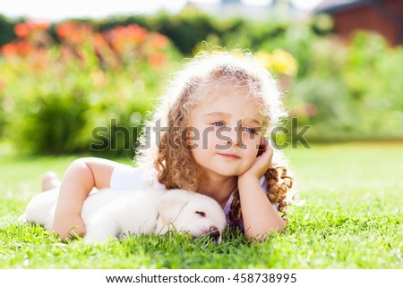Little girl with a labrador puppy, outdoor summer