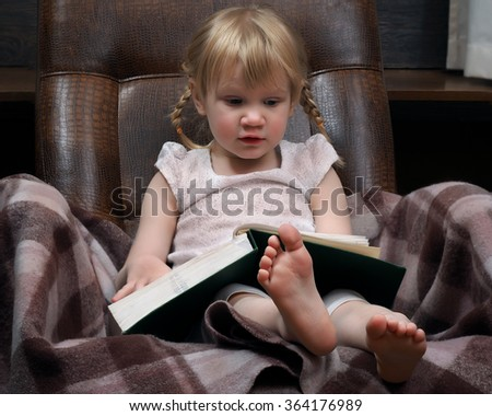 Little girl with a large book. Green Book. The girl in the chair. A girl with two braids, wearing a white dress, barefoot. The plaid chair. Girl learns to read. Portrait of a young child